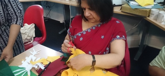 a woman in a sari cutting yellow felt