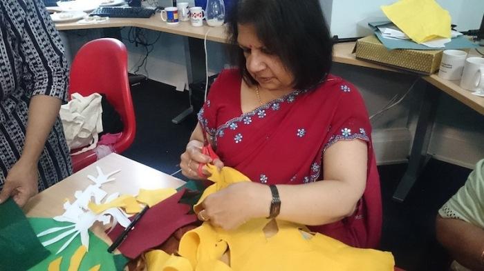 a woman in a sari cutting yellow felt
